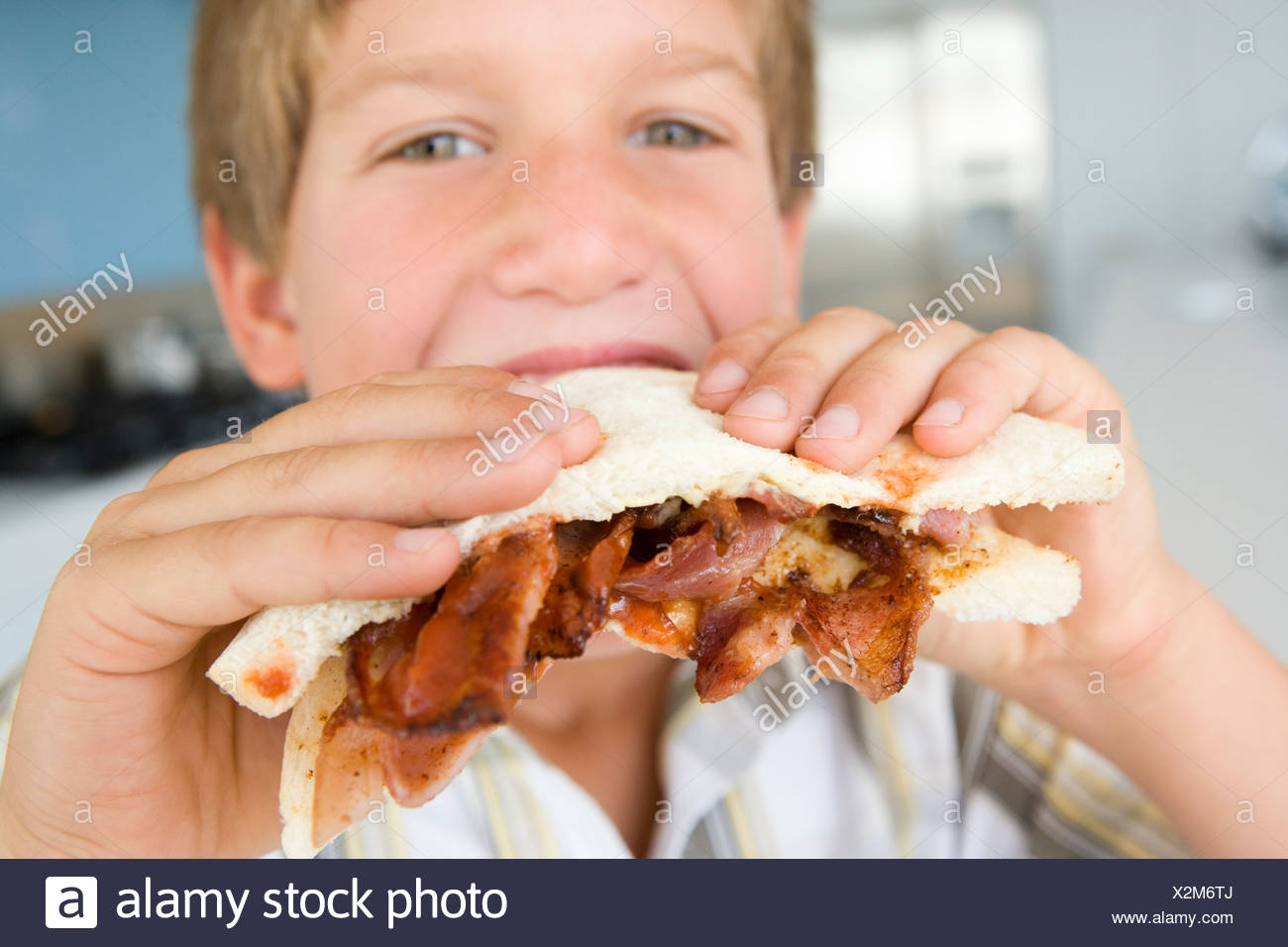 Young boy in kitchen eating bacon sandwich - Stock Image