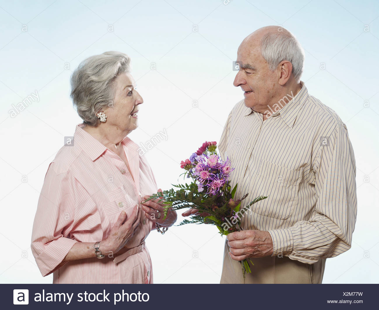 Senior man gives senior woman flowers Stock Photo