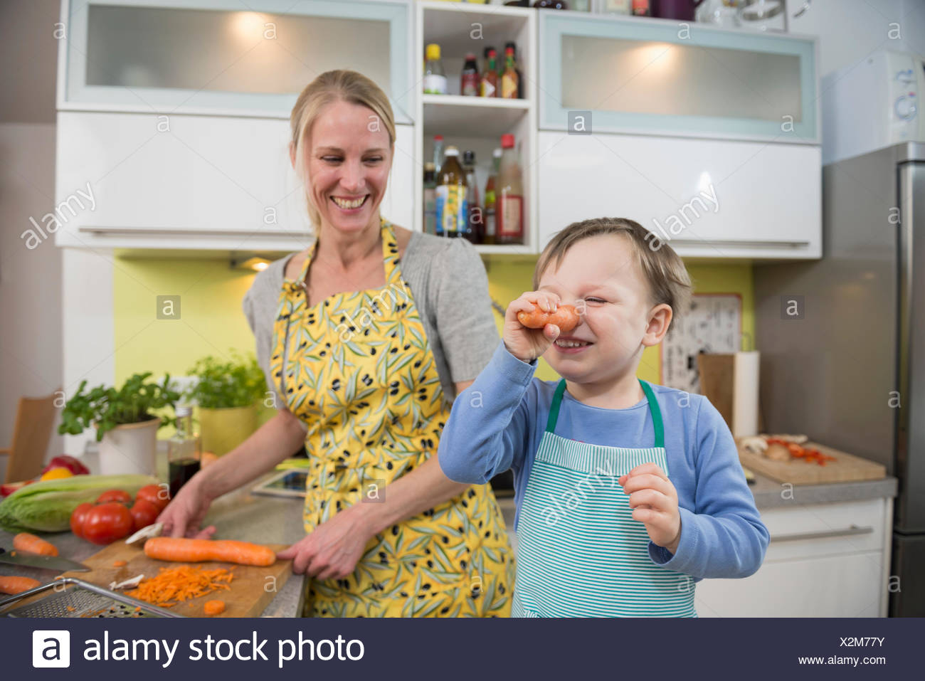 Boy fool around with carrots while mother is laughing - Stock Image