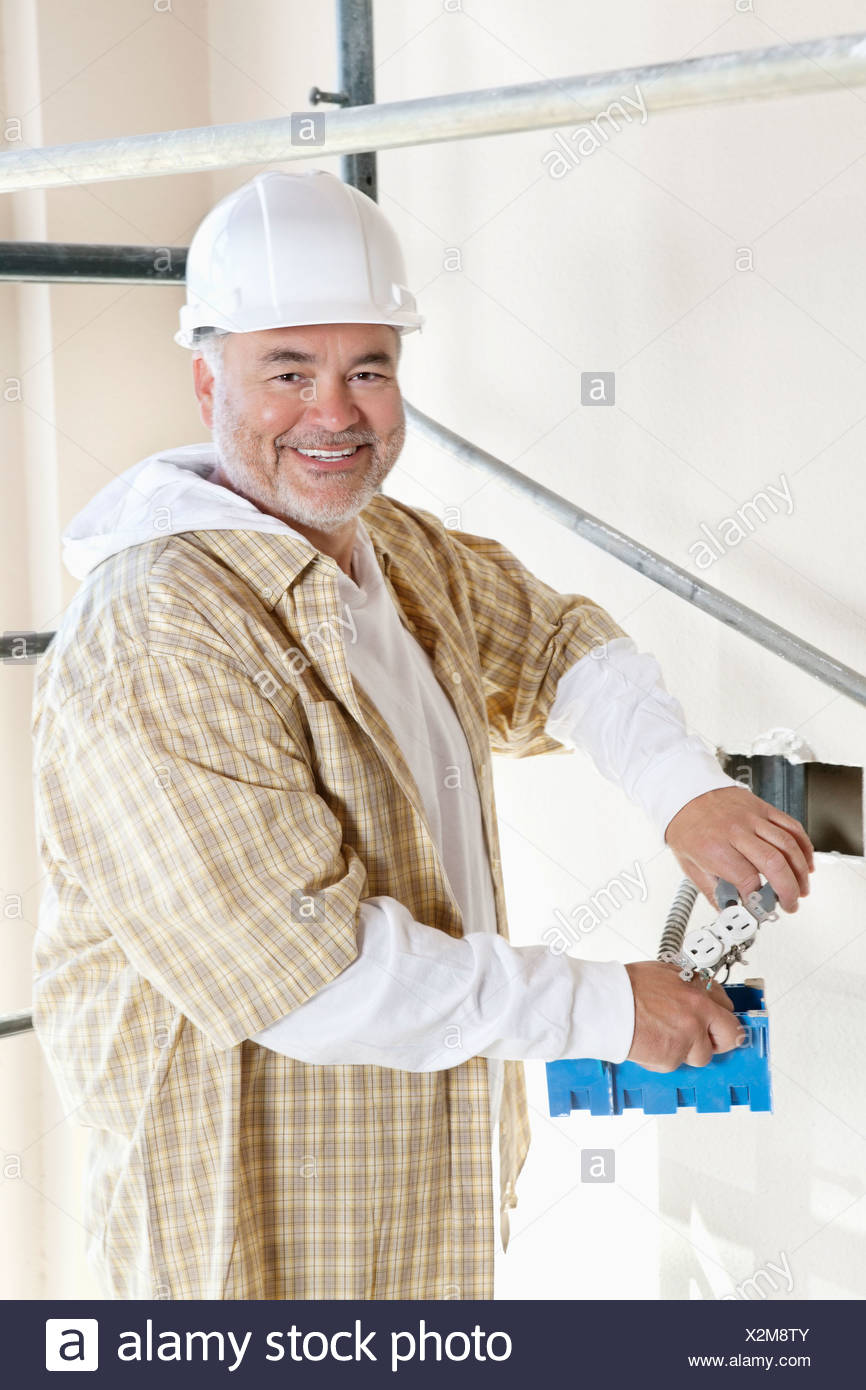 Portrait of a cheerful mature man holding construction equipment Stock Photo