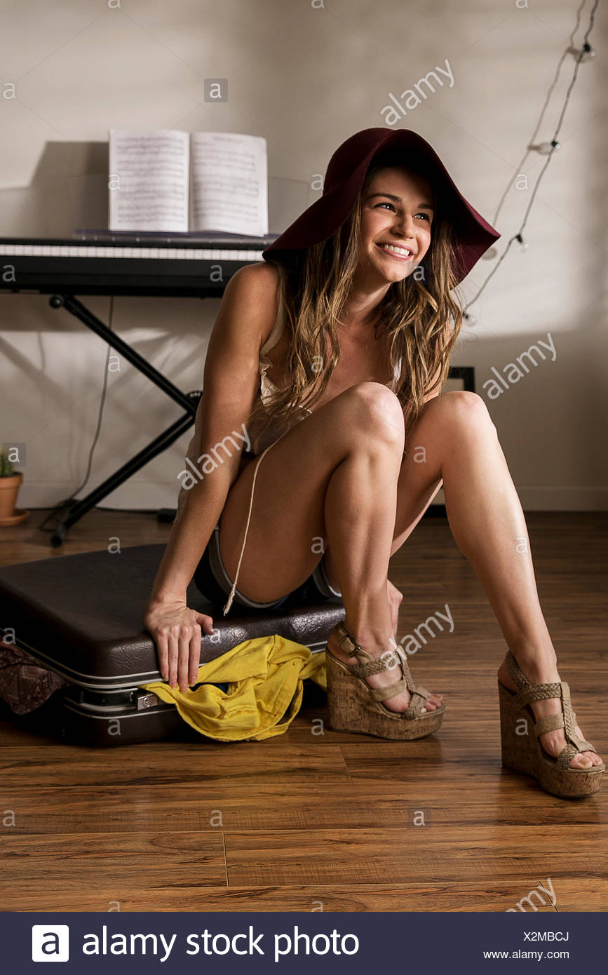 Portrait of young woman sitting on top of suitcase - Stock Image