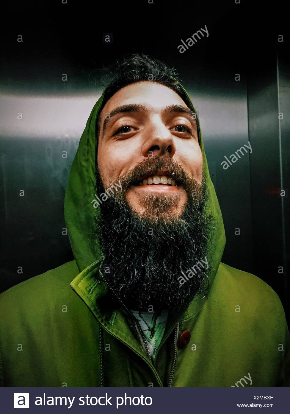 Young Cheerful Man With Long Beard In Elevator - Stock Image