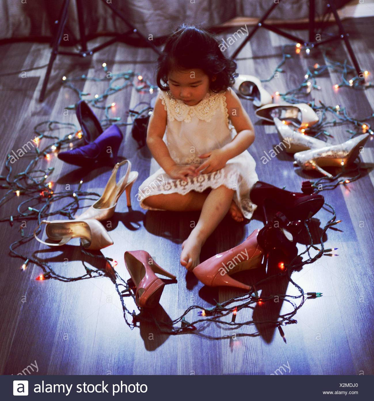 Girl Sitting Amidst High Heels And Christmas Lights On Hardwood Floor - Stock Image