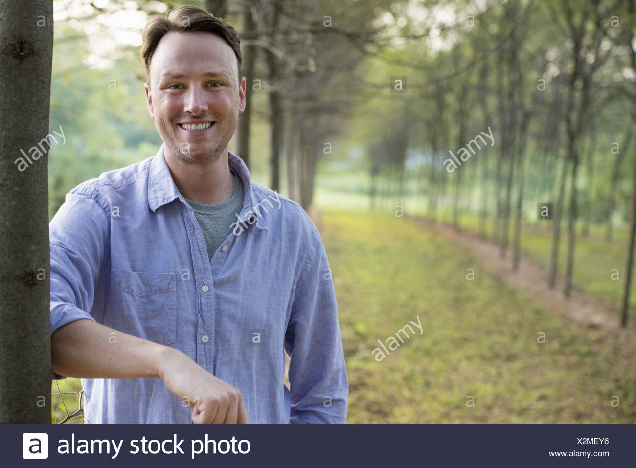 A man leaning against a tree looking at camera. - Stock Image