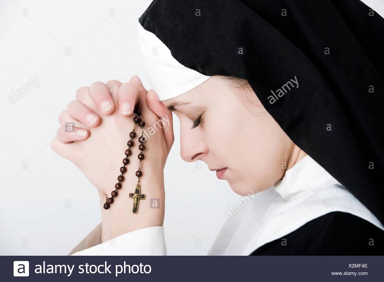 young nun praying the rosary - Stock Image