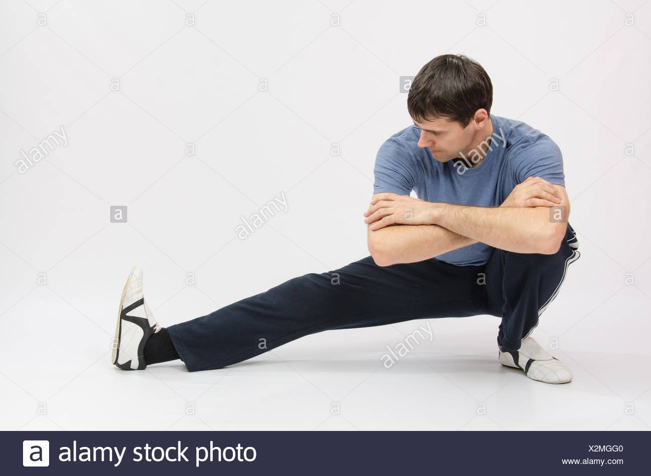 Athlete Crouching Stretches Muscles Of Left Leg Stock Photo