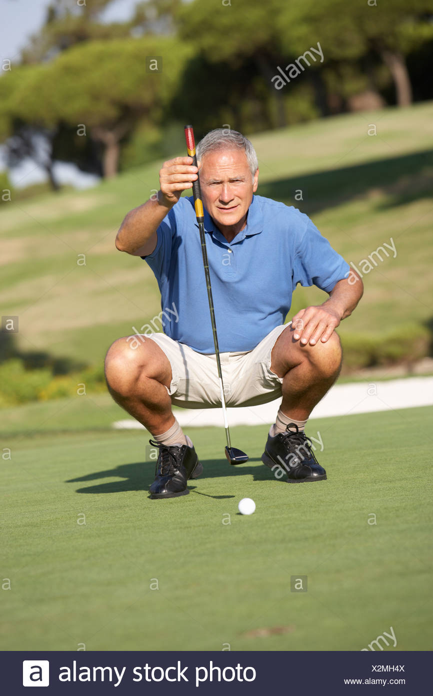 Senior Male Golfer Golf Course Putt Green - Stock Image