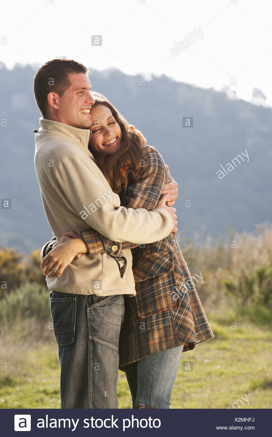 Young couple embracing in rural scene Stock Photo