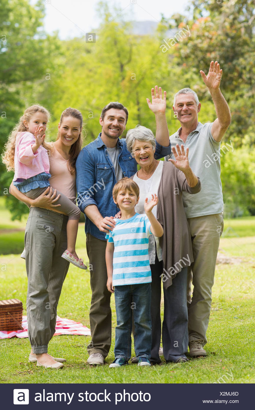 Extended family waving hands in park - Stock Image