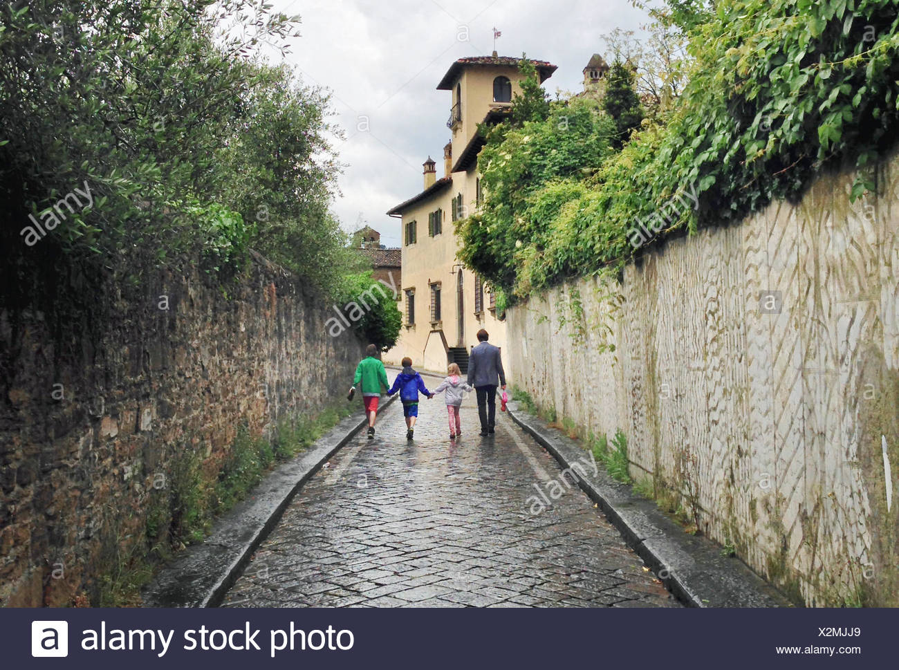 Italy, Tuscany, Florence, Father with three kids (10-11, 12-13) walking on rainy day - Stock Image