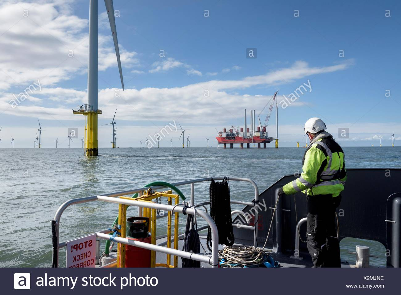 Worker looking out from ship to offshore wind farm and construction ship - Stock Image