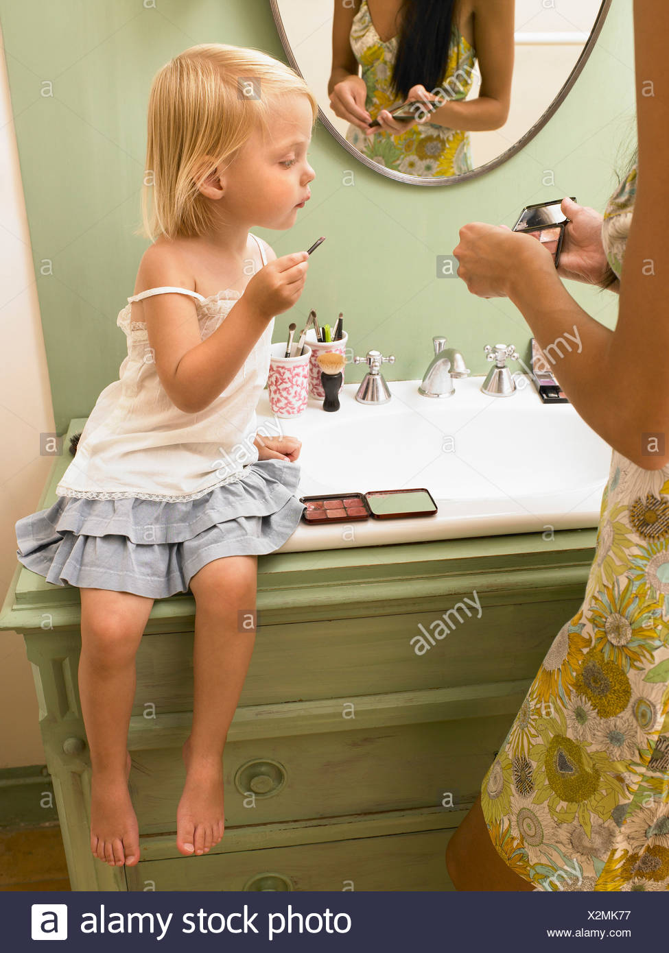 Mother and daughter applying makeup. - Stock Image