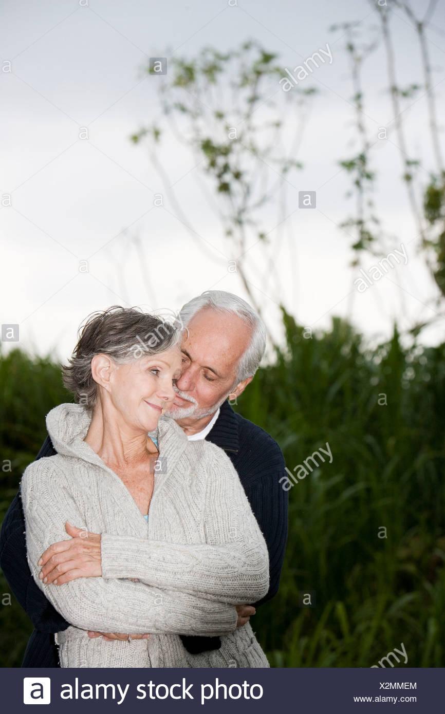 Senior couple smiling and embracing - Stock Image