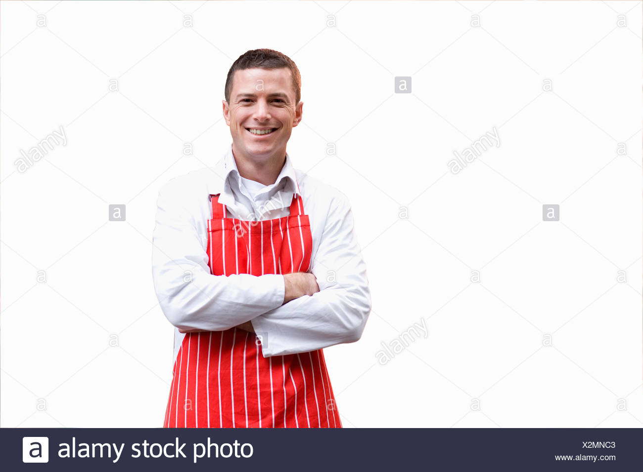Smiling butcher in apron with arms crossed - Stock Image