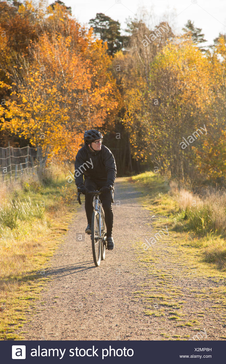 Sweden, Vastergotland, Lerum, Mature man riding bicycle on dirt road through autumn forest - Stock Image
