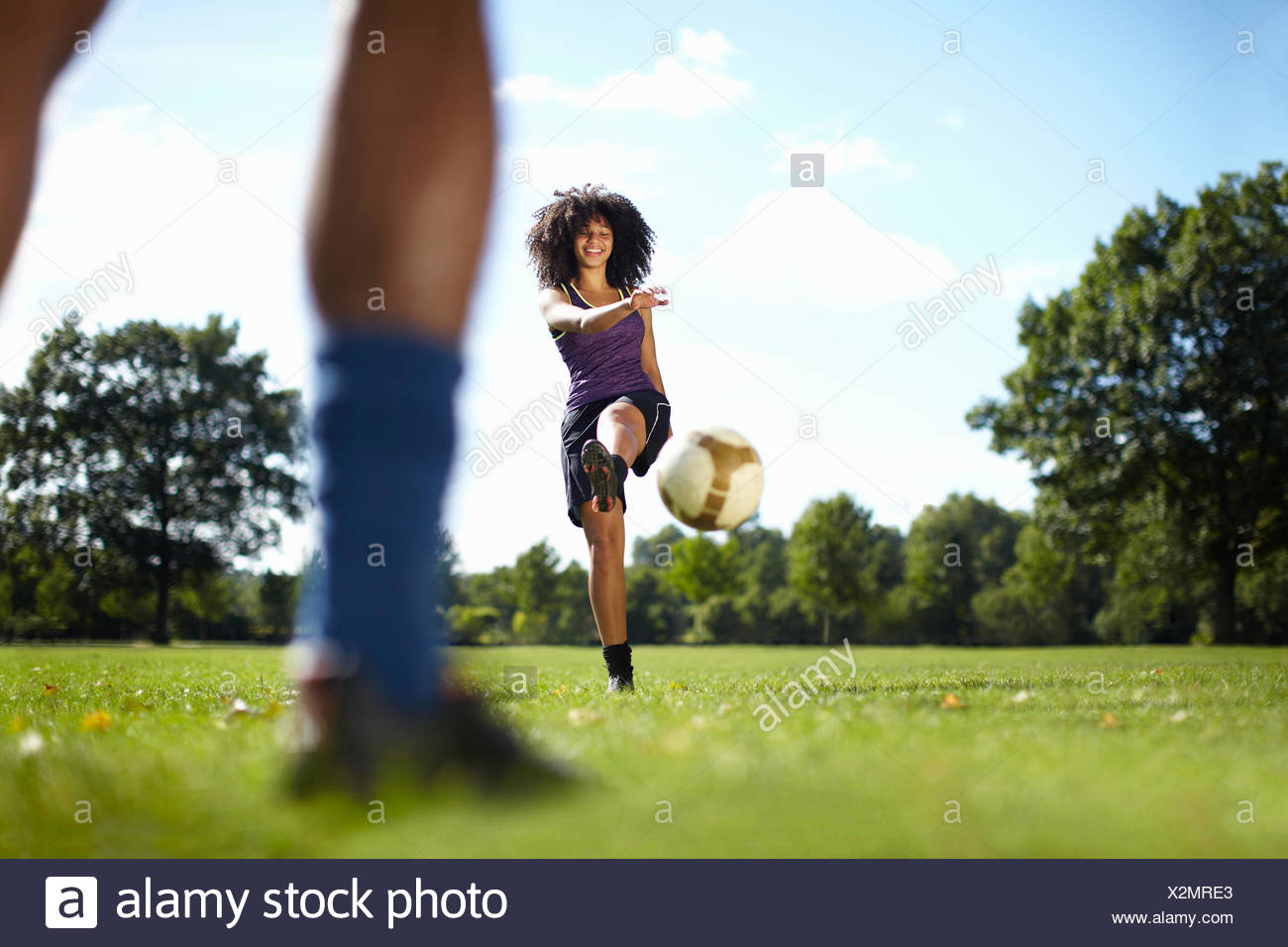 Young woman kicking soccer ball toward boyfriend in park - Stock Image