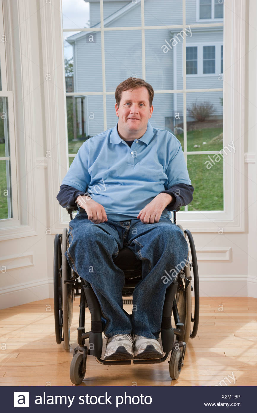 Man with spinal cord injury in a wheelchair smiling in his accessible home - Stock Image