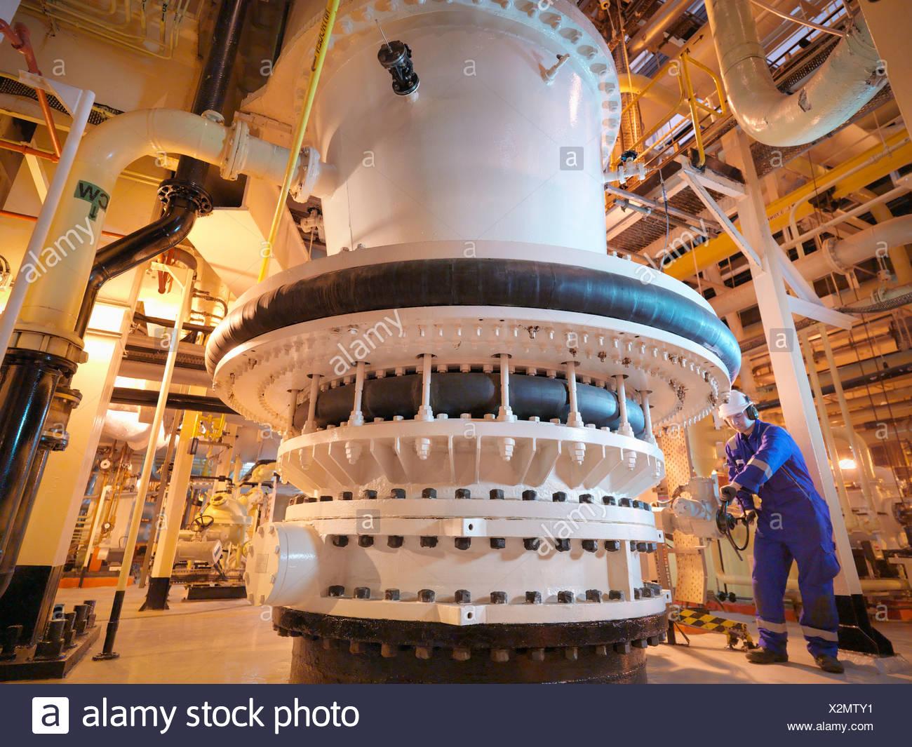 Engineer adjusting seawater valve in power - Stock Image