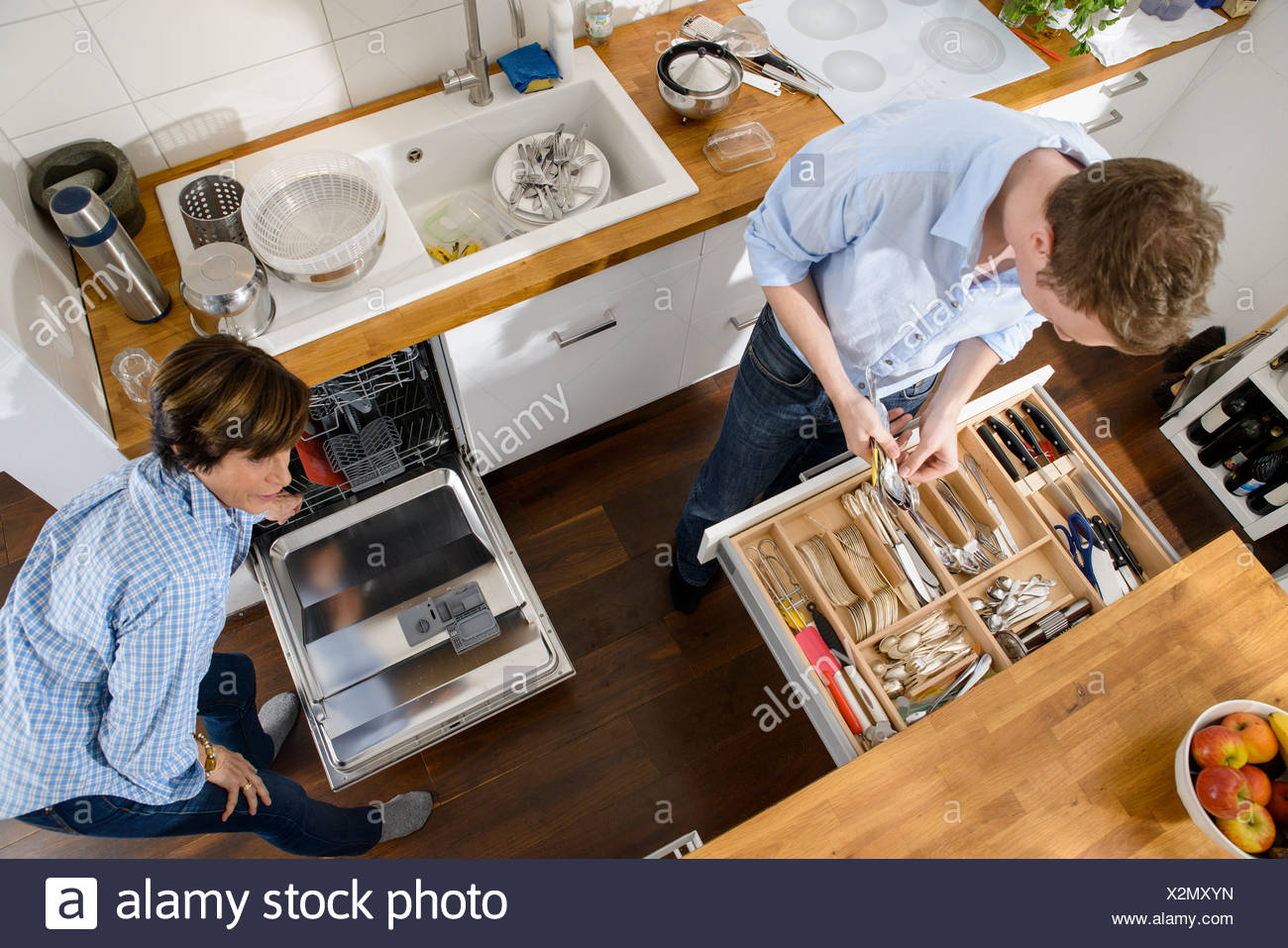 Grandmother and adult grandson tidying away cutlery from dishwasher - Stock Image