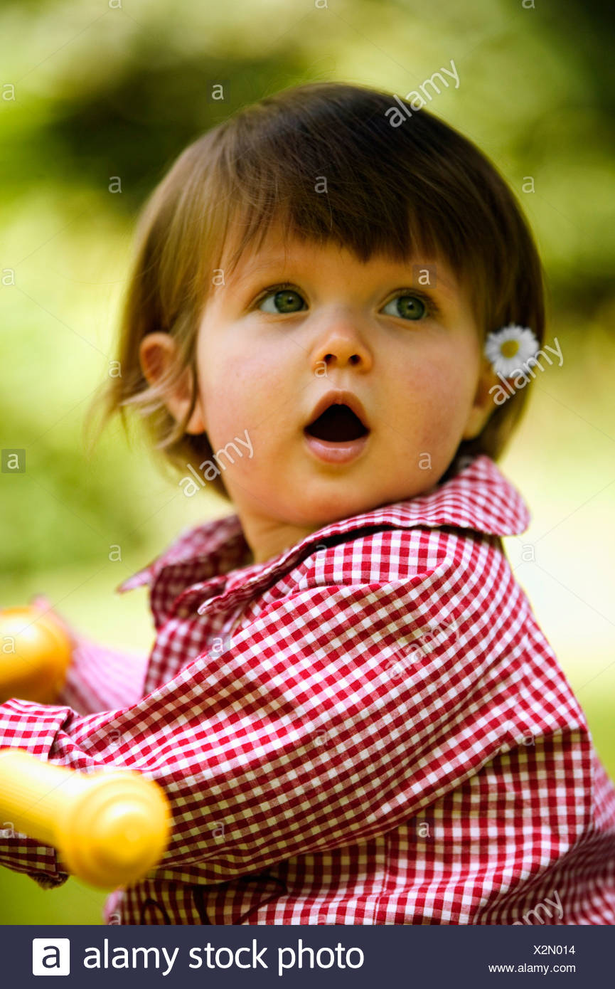 Baby girl with daisy tucked behind her ear - Stock Image