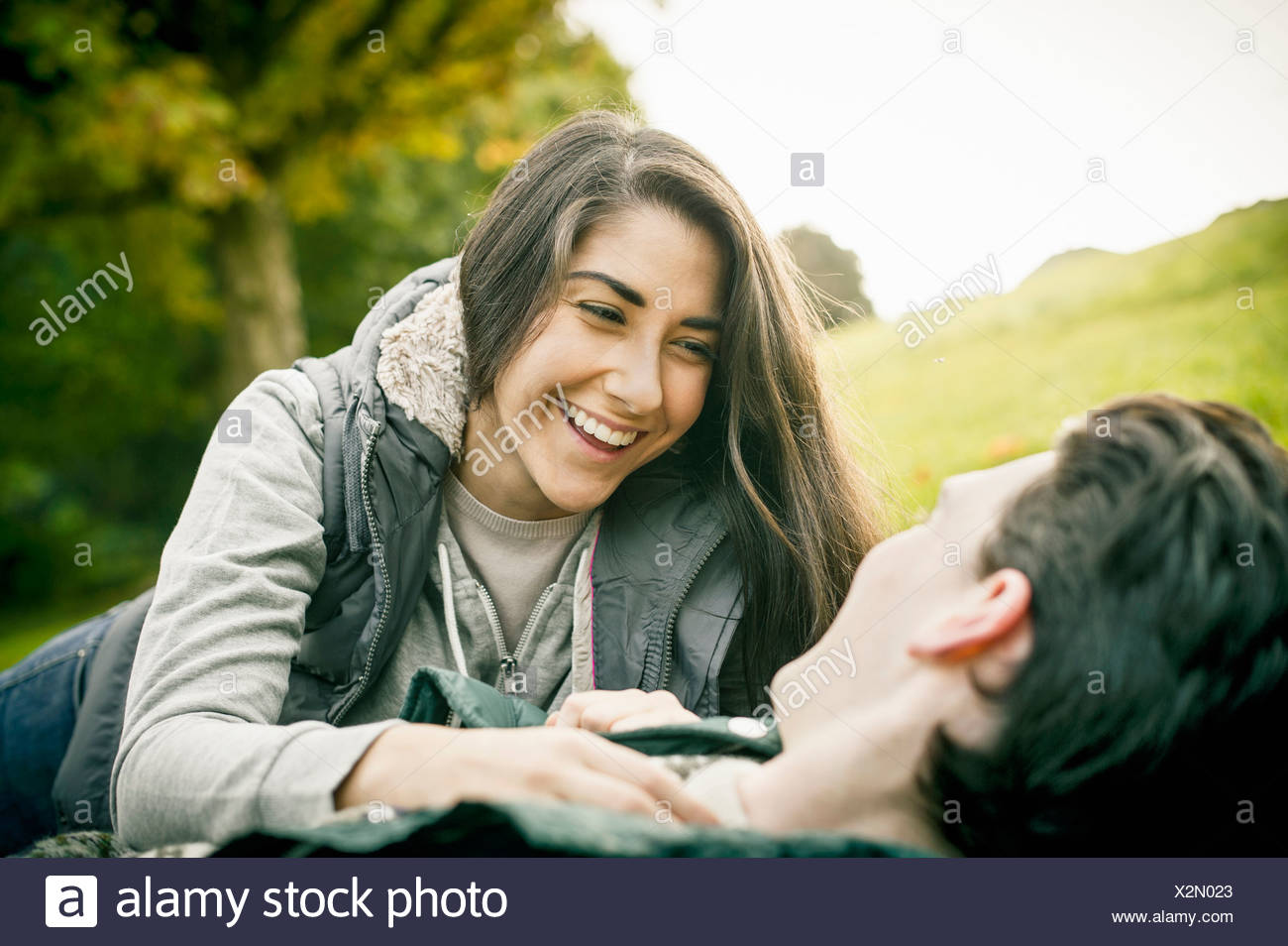 Young couple in park, laughing - Stock Image