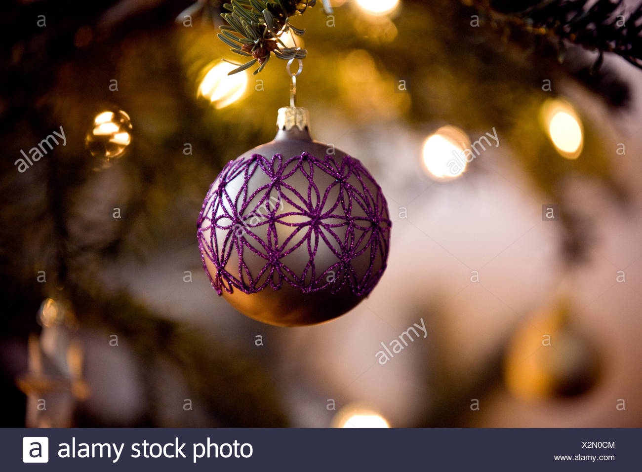 a purple and gold bauble hanging on a christmas tree stock image