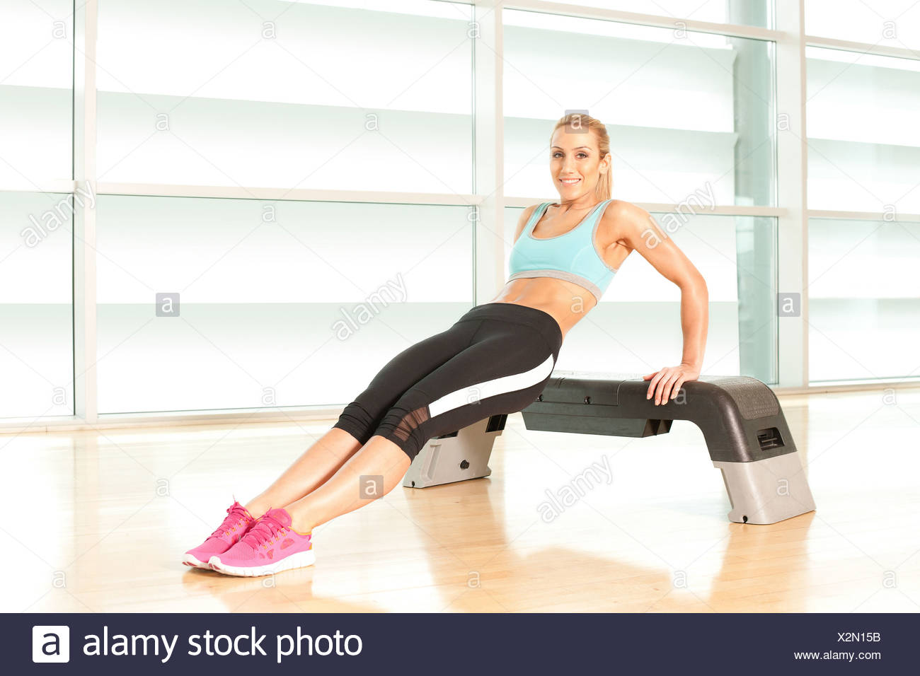 Woman exercising on step - Stock Image