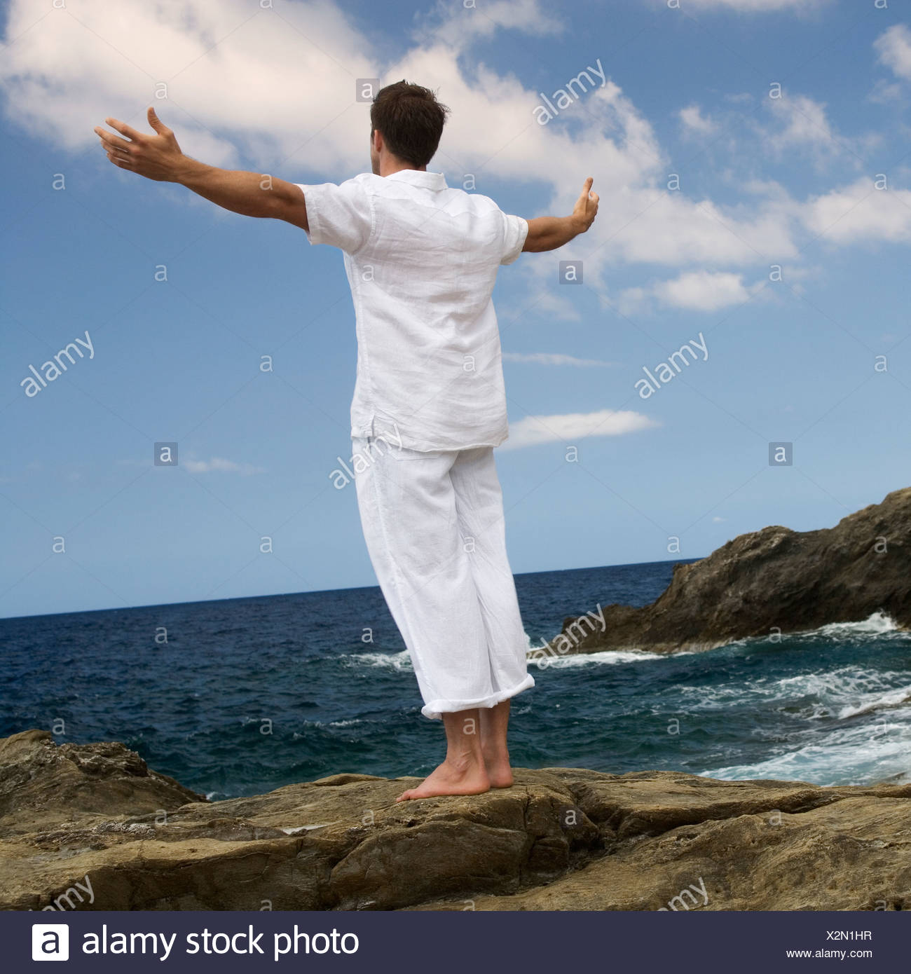 A man stretching on the rocks by the sea - Stock Image