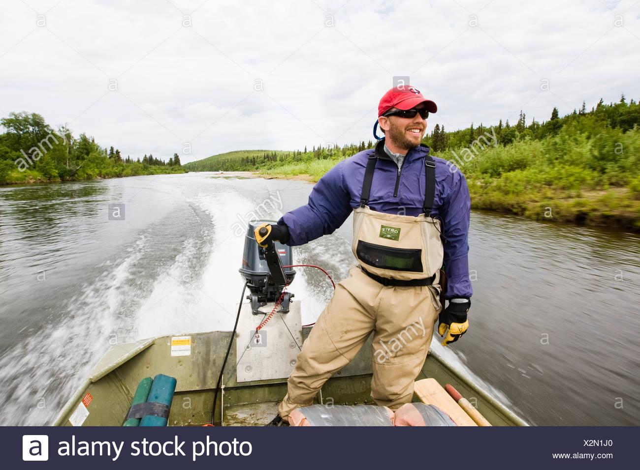 Sportfishing guide drives powered skiff on the Koktuli River in the Bristol Bay area, Southwest Alaska, Summer - Stock Image