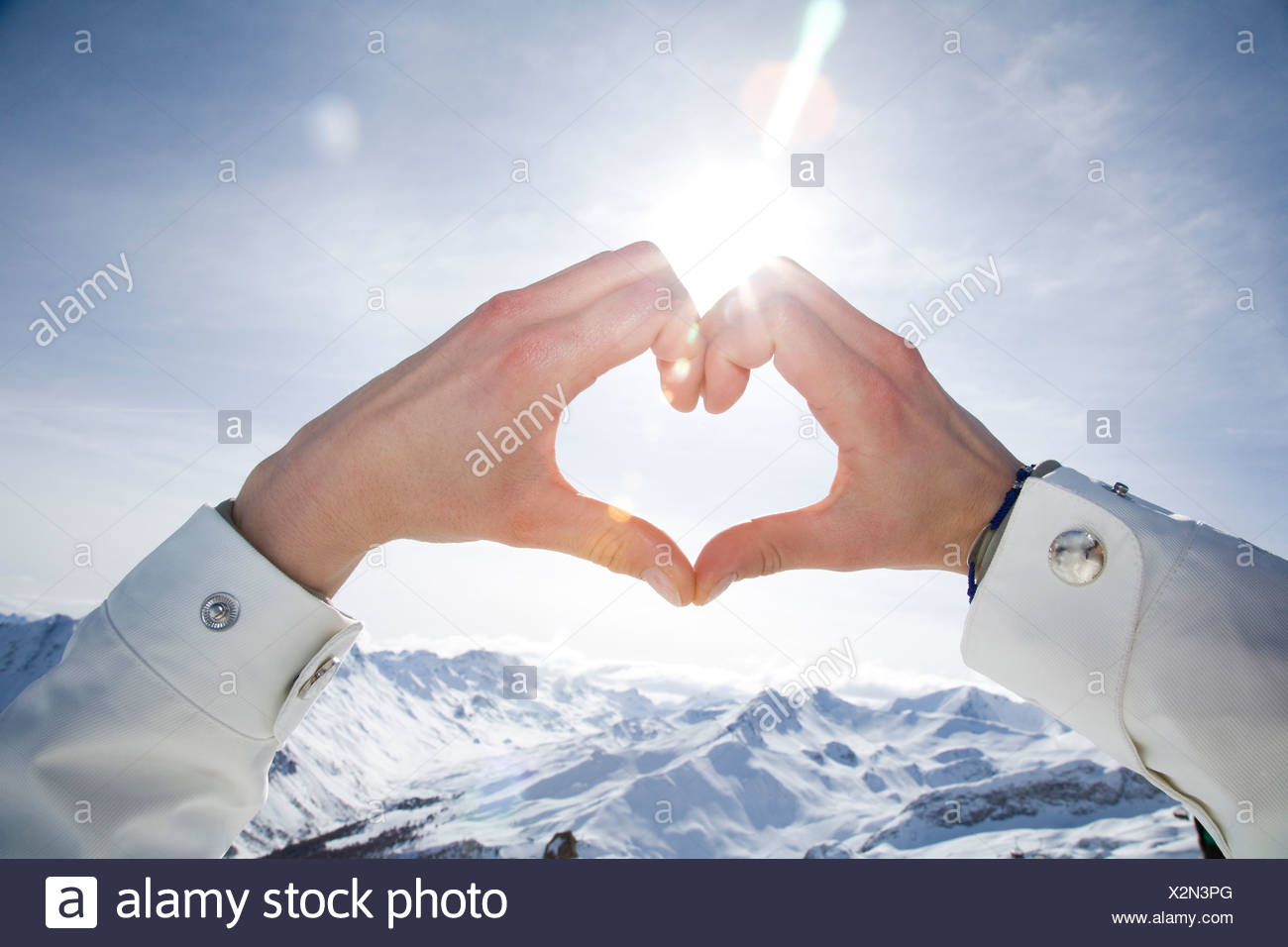 Close-up of woman's hands making heart shape over snow-capped mountains - Stock Image