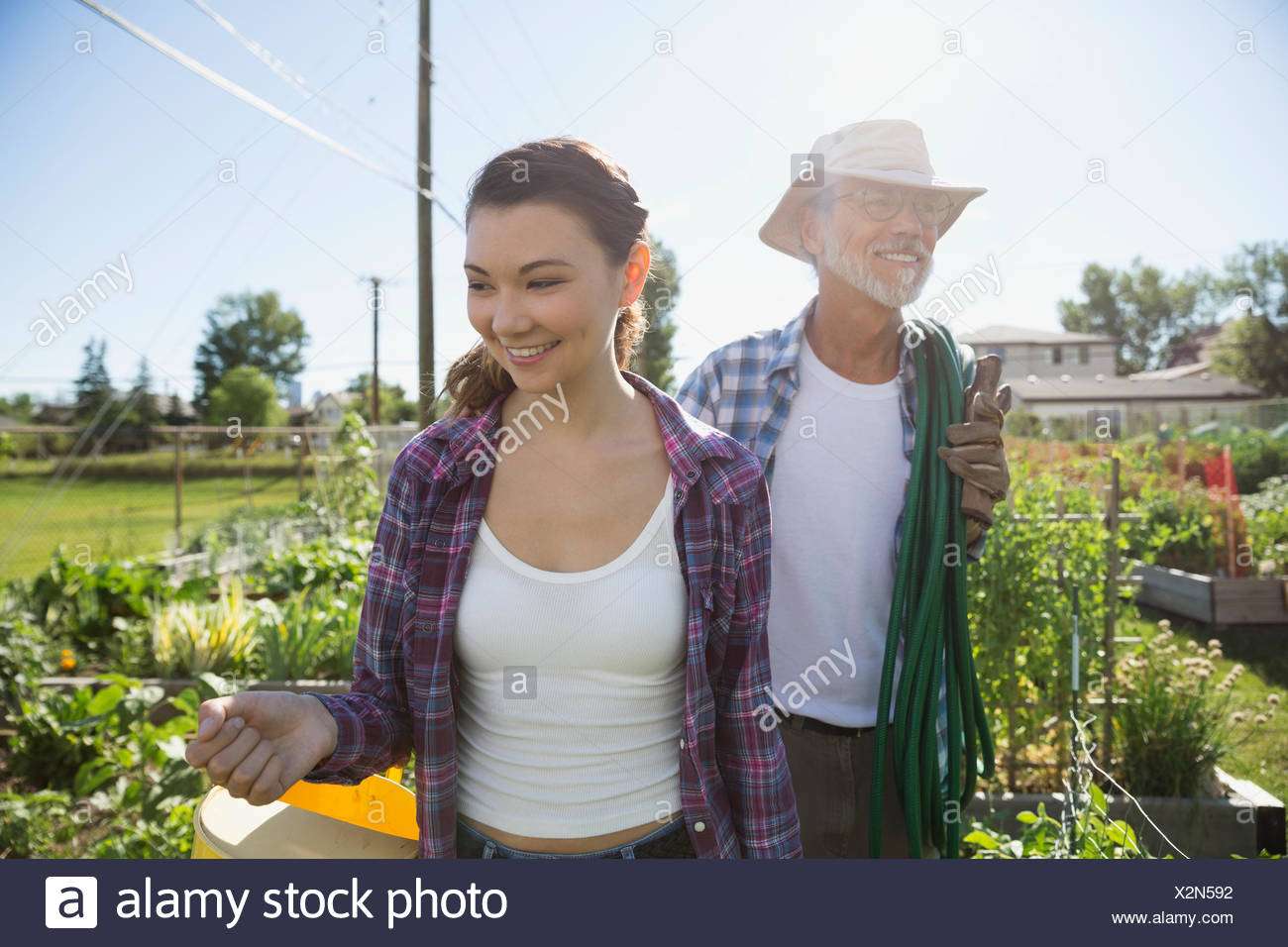 Smiling father and daughter in sunny garden - Stock Image