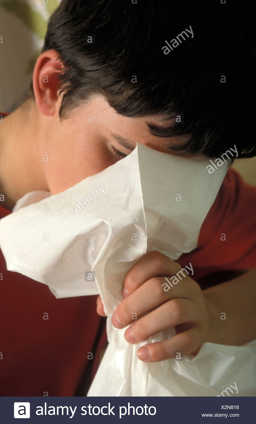teenage boy inhaling solvents from paper bag - Stock Image