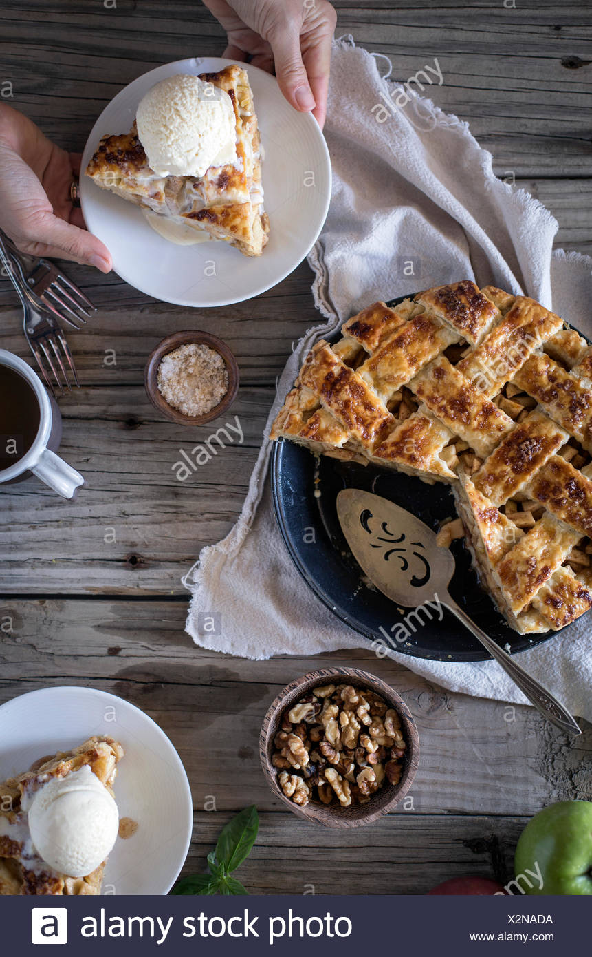 A slice of apple pie is being served by a woman on a farm style table. - Stock Image
