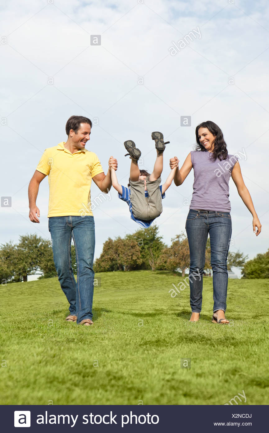 Germany, Bavaria, Parents playing with son in park, smiling - Stock Image