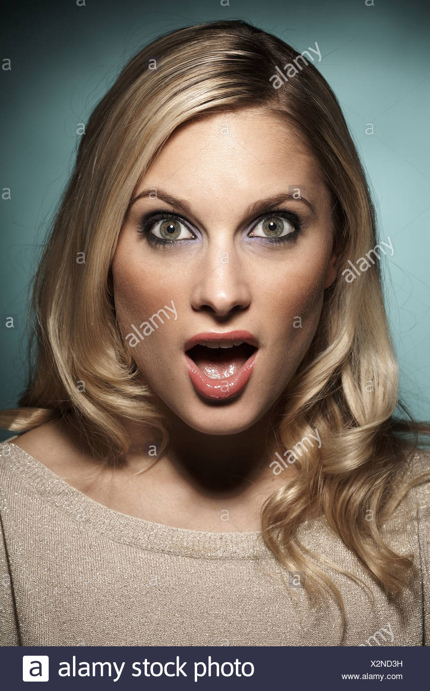 Female with mouth and eyes wide open looking shocked - Stock Image