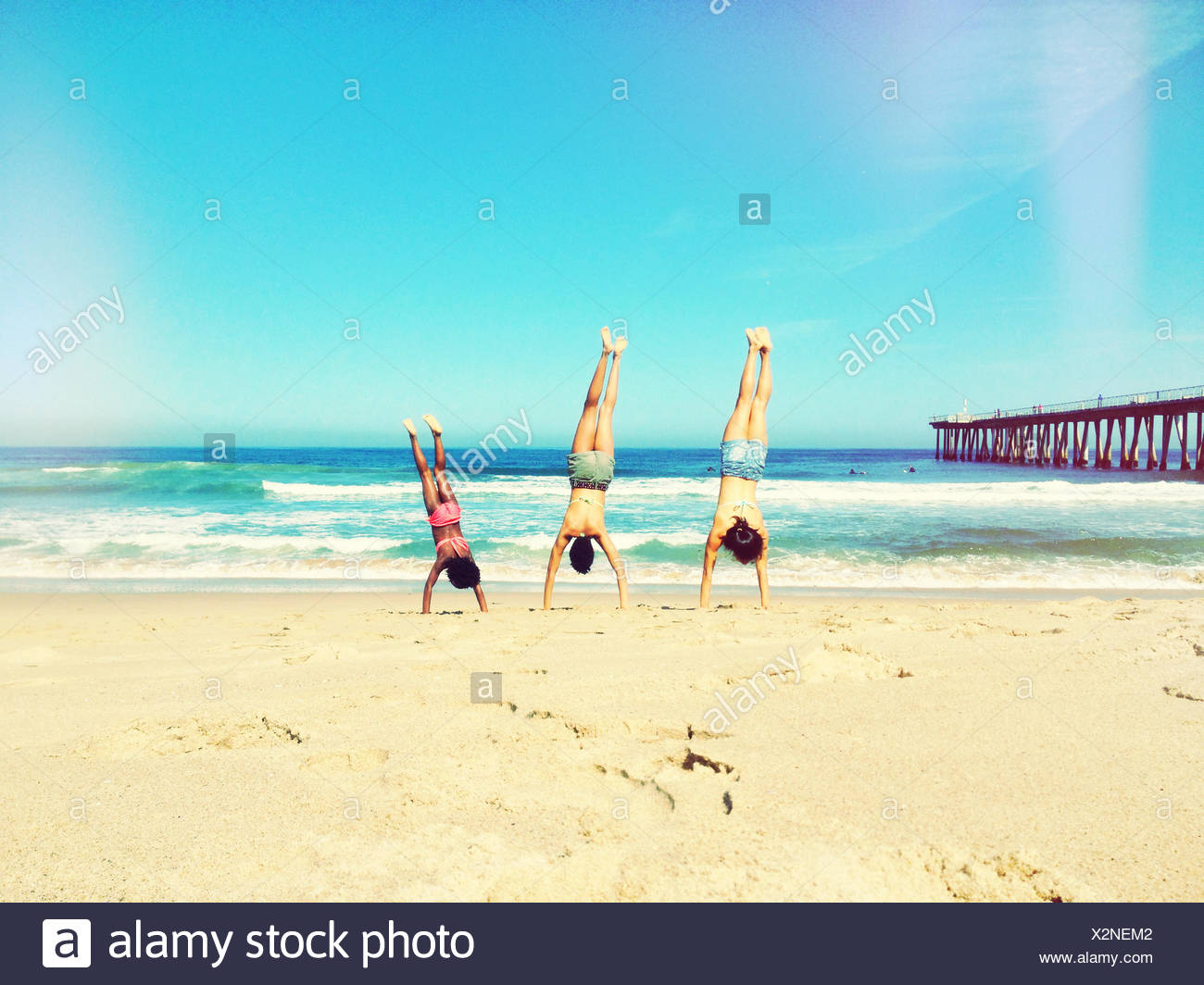 Mother, father and daughter doing handstand on beach - Stock Image