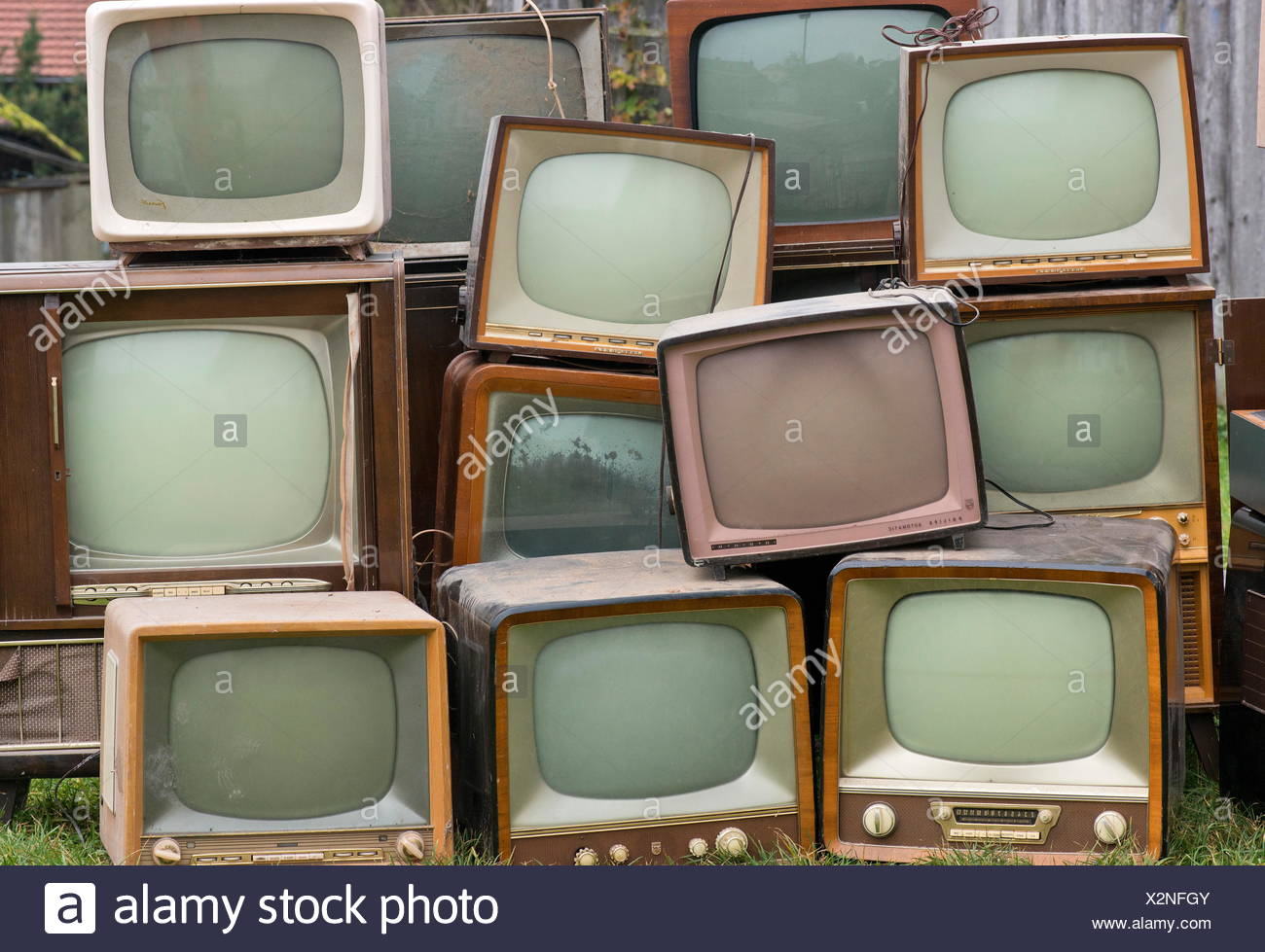 broadcast, television, old German television sets by Neckermann, Saba, Grätz, Philips, Nordmende, Vega, Germany, 1950s and 1960s, piled in the meadow, television wall, wall of tv sets, monitor wall, wall of monitors, television collection, collection of tv sets, television set collection, strange, screen size, screens, telescreen, TV screen, defect, fault, defects, defective, faulty, damaged, broken, e-waste, waste disposal, television receiver, TV history, destroyed, consumer good, consumer item, consumer goods, consumer items, Made in Germany, medium, media, , Additional-Rights-Clearences-NA - Stock Image