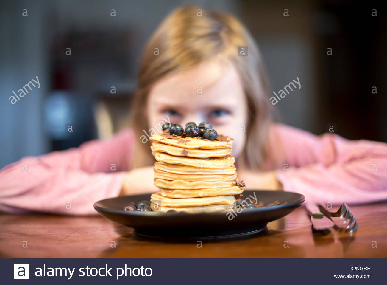 Plate with stack of pancakes with little girl in the background - Stock Image