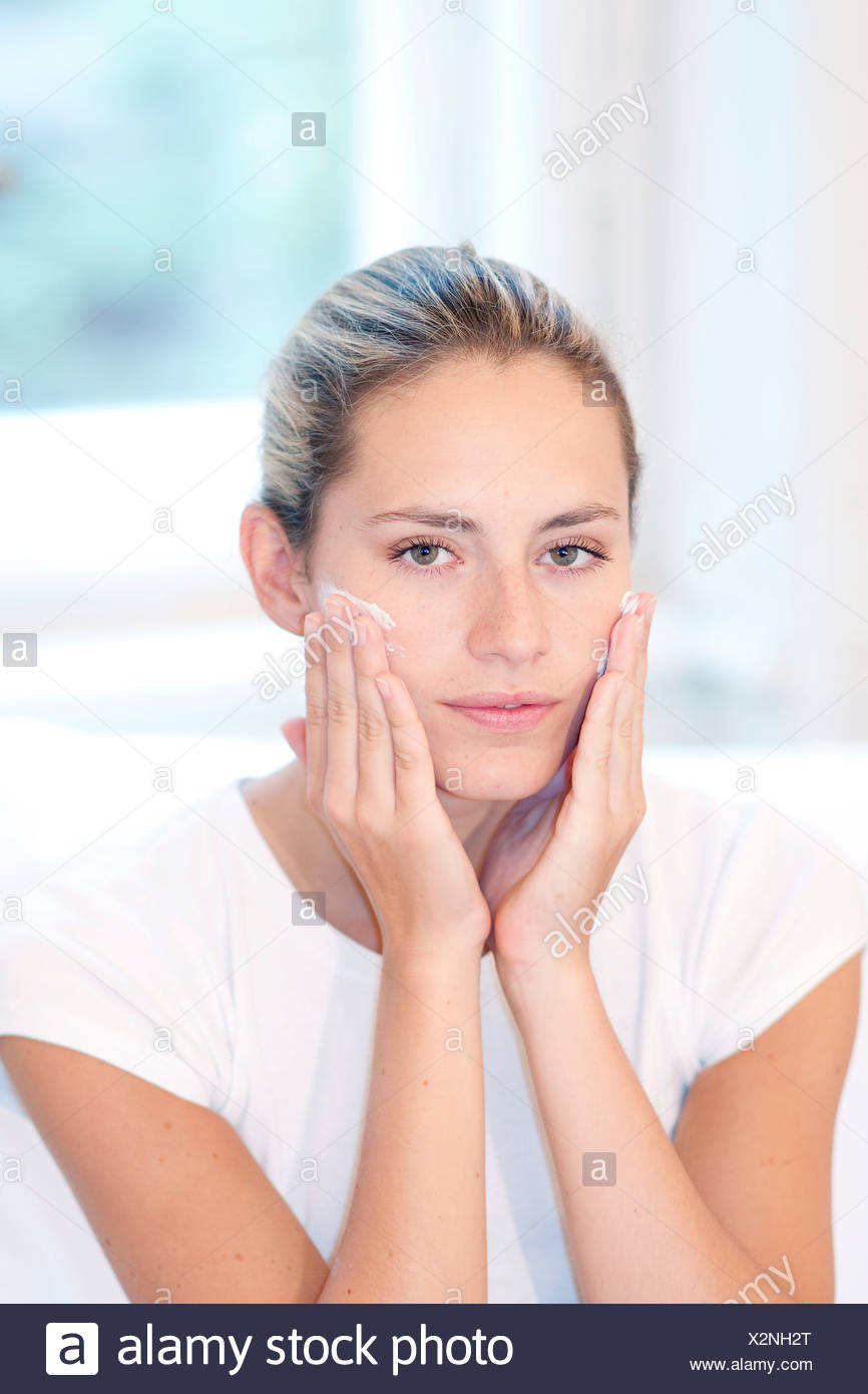 Female highlighted fair hair off her face, wearing a white t shirt, applying face cream to her cheeks, unsmiling, looking at - Stock Image
