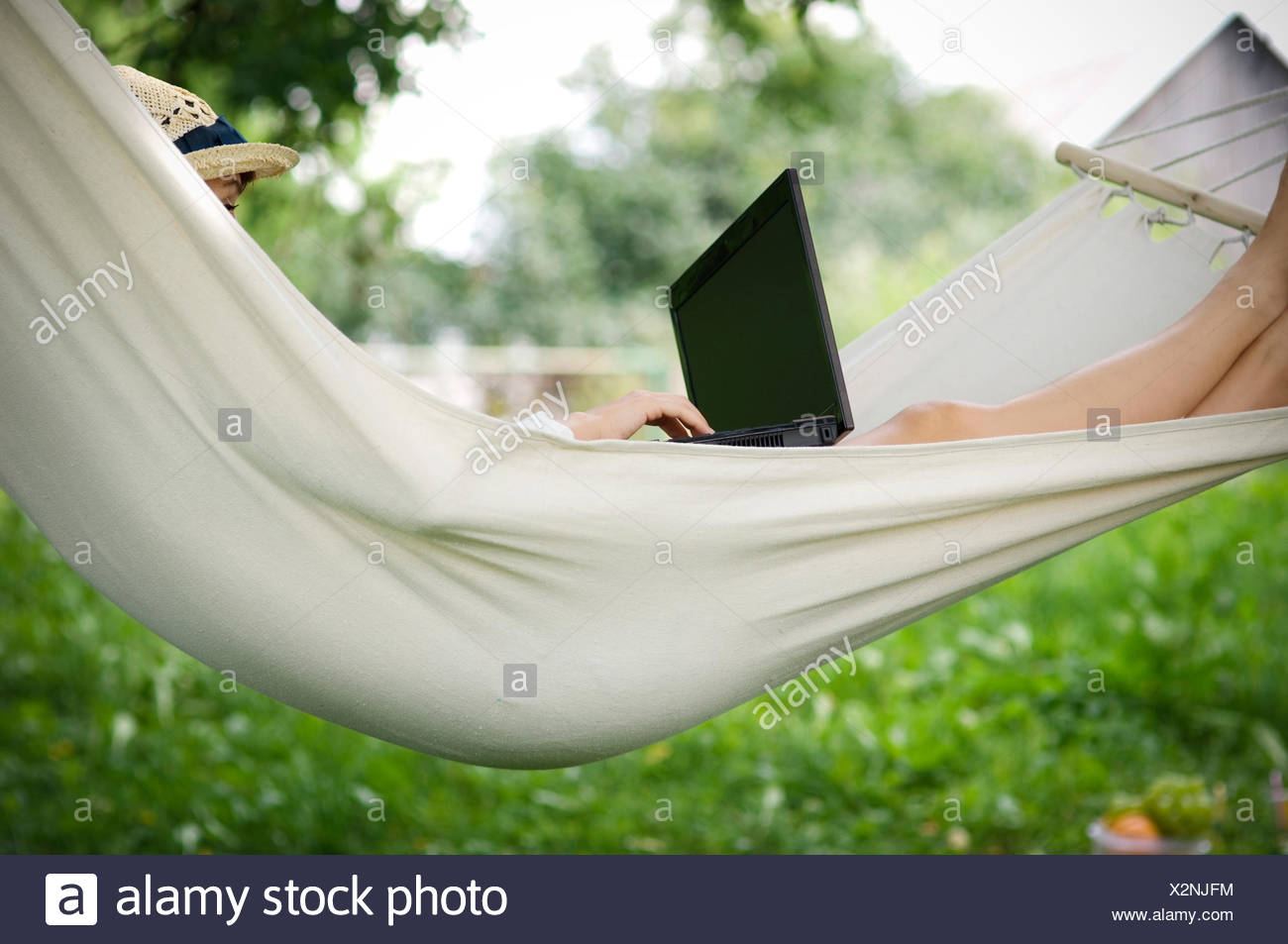 Young woman working on hammock with laptop, Debica, Poland. - Stock Image