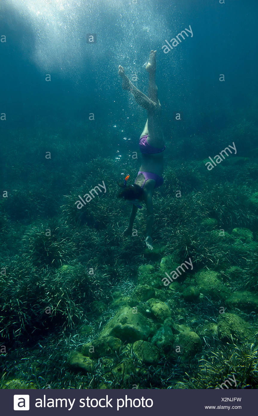 Woman with a snorkel and diving goggles scuba diving in the sea, underwater picture, Villasimius, Sardinia, Italy, Europe - Stock Image
