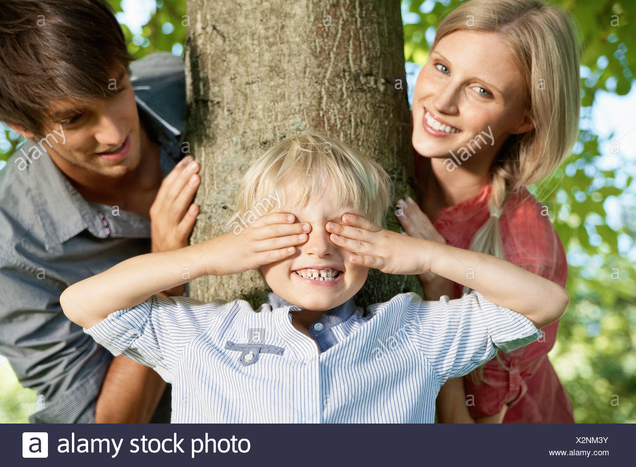 Germany, Cologne, Boy playing hide and seek with parents Stock Photo