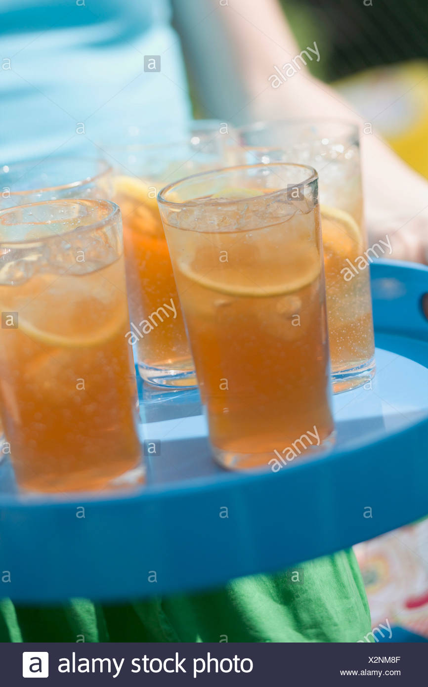 Person serving several glasses of iced tea on a tray - - Stock Image