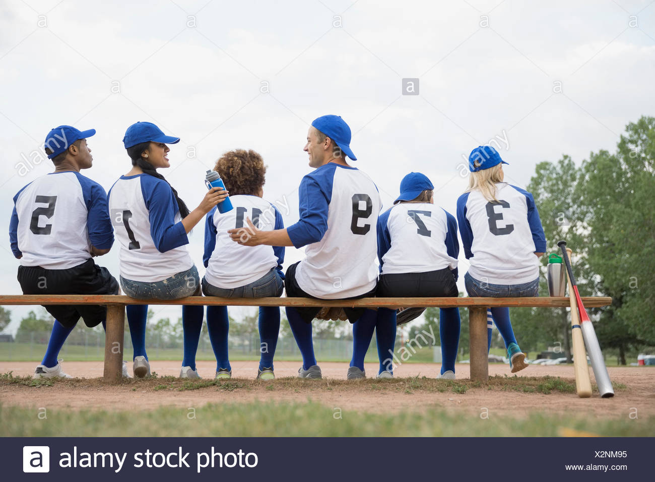Baseball team sharing water on bench in field - Stock Image