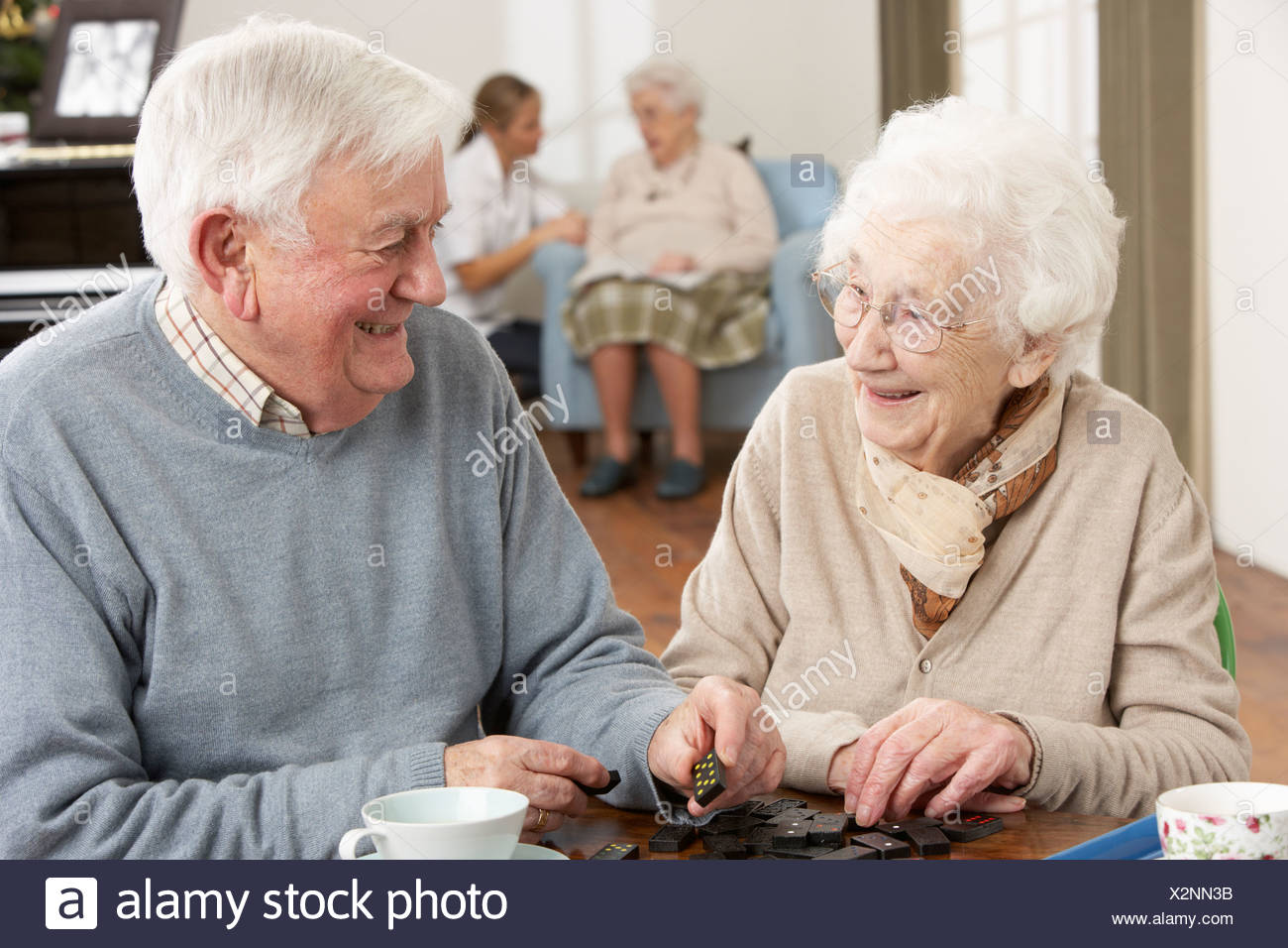 Couple Playing Dominoes At Day Care Centre - Stock Image