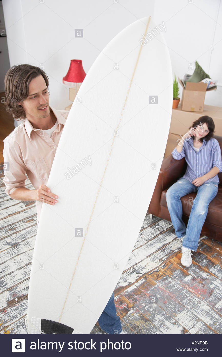 Man with surf board in home with boxes and woman on sofa - Stock Image