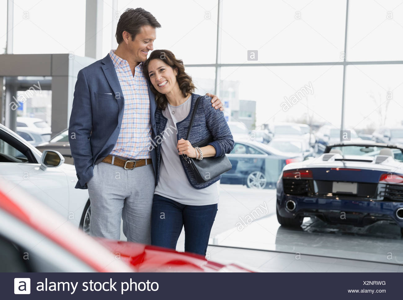 Couple hugging in car dealership showroom Stock Photo