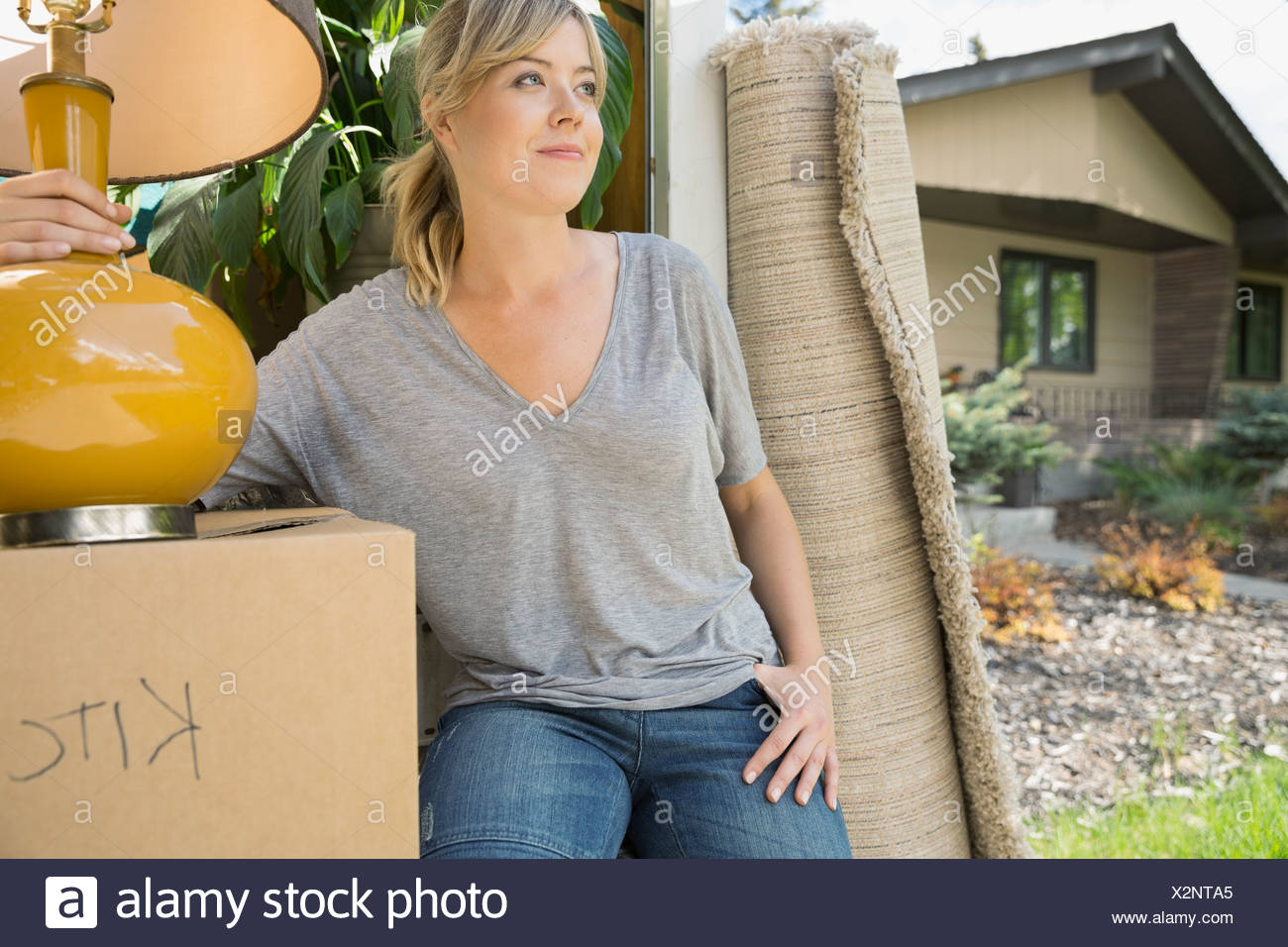 Woman unloading belongings from moving van Stock Photo
