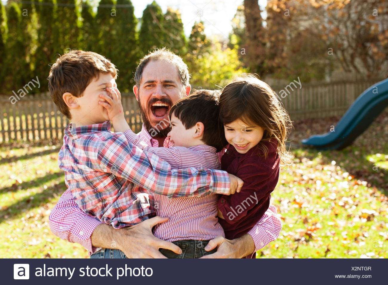 Father carrying playful children in his arms, open mouthed looking surprised - Stock Image