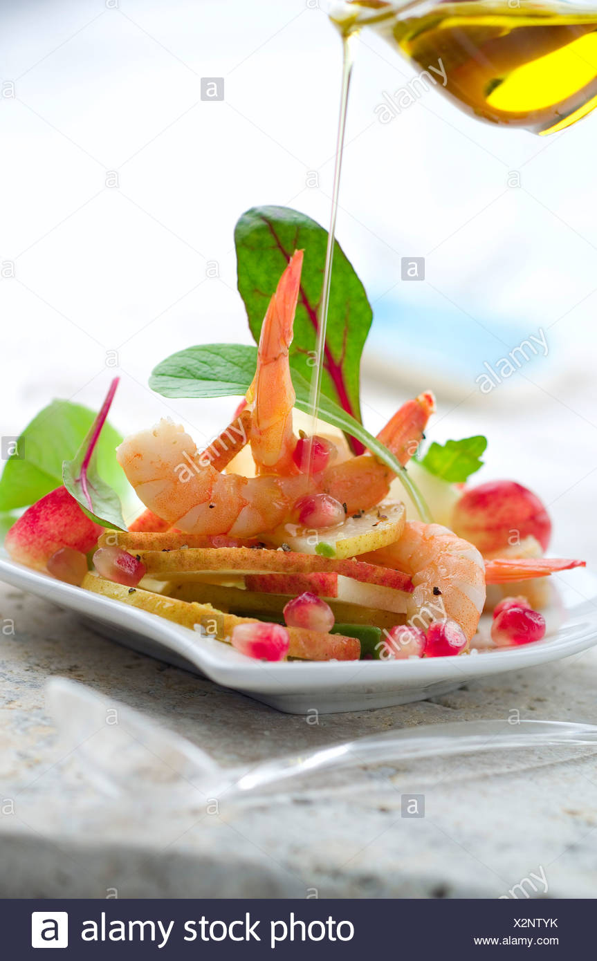 Pouring a drop of olive oil onto the pear and shrimp salad - Stock Image